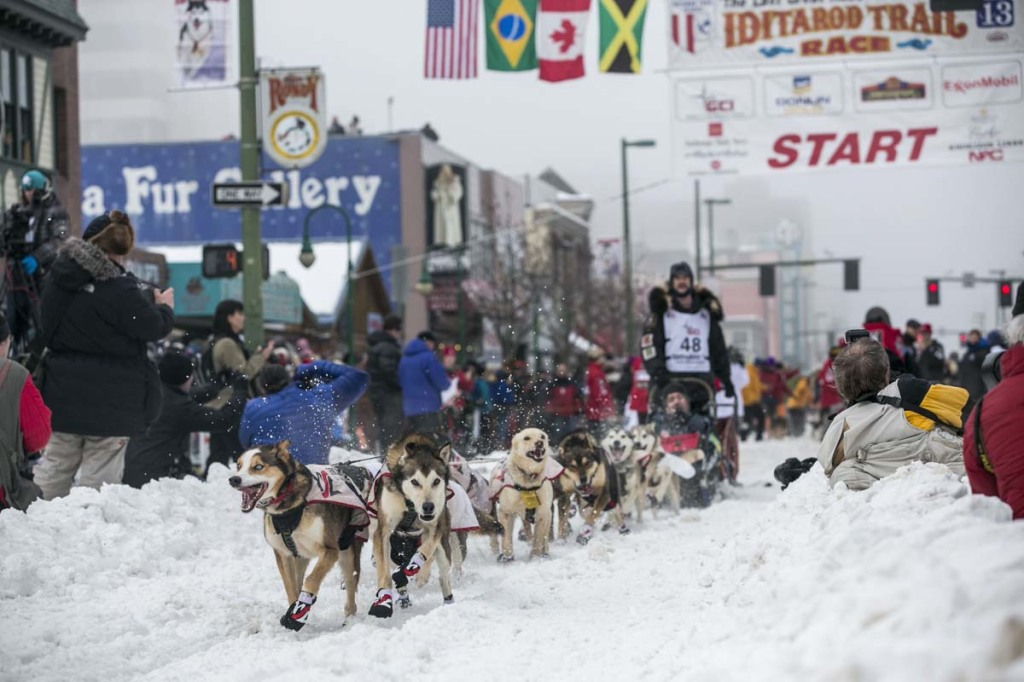Moore's team charges out of the starting gate on 4th Avenue during the ceremonial start to the Iditarod dog sled race in downtown Anchorage, Alaska
